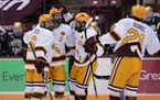 Gophers defenseman Jackson LaCombe (2) celebrated with teammates Mike Koster (6), left, and Jack Perbix (25) after scoring a goal during the first per