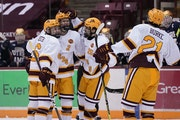 Gophers  defenseman Jackson LaCombe (2) celebrated with teammates after scoring a goal during the first period Friday.