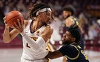 Minnesota forward Brandon Johnson (23) grabbed a rebound as Michigan guard Mike Smith (12) defended in the first half.
