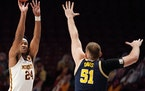 Minnesota forward Eric Curry took an outside shot over the head of Michigan forward Austin Davis.