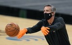 San Antonio Spurs assistant coach Chip Engelland wears a face mask and gloves to protect against the spread of COVID-19 as he helps the team warm up