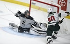 Los Angeles Kings goalie Jonathan Quick, left, stretches to block a shot by Minnesota Wild center Marcus Johansson during the first period