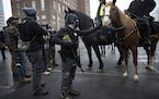 Members of the Ohio Boogaloo Boys pet a police horse outside of the Ohio Statehouse in Columbus, Ohio., Jan. 17, 2021. Across the country, officials w