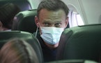 Alexei Navalny sits on the plane prior to a flight to Moscow, at the Airport Berlin Brandenburg in Schoenefeld, near Berlin, Germany, Sunday, Jan. 17,
