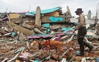 A police officer leads a sniffer dog during a search of victims at the ruin of a building flattened by an earthquake in Mamuju, West Sulawesi, Indo