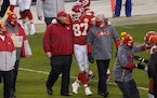 Kansas City Chiefs tight end Travis Kelce (87) walks off the field with head coach Andy Reid after an NFL divisional round football game against the C