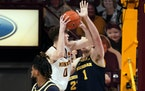 Minnesota's Liam Robbins (0) eyes the basket as Michigan's Hunter Dickinson (1) defends in the second half on Saturday.