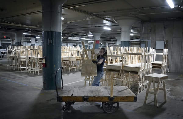 Kate Hersey, Minnesota Tool Library executive director, with some of the 600 desks for students made at the Minnesota Tool Library's two branches, a