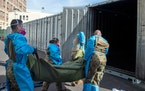 This Jan. 12, 2021, file photo provided by the LA County Dept. of Medical Examiner-Coroner shows National Guard members assisting with processing COVI