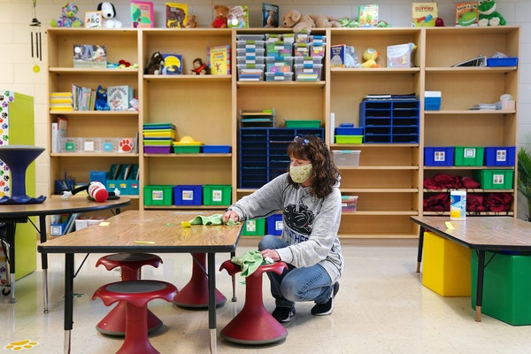 Kindergarten teacher Kate Boynton scrubbed the desks in her classroom last week at Oxbow Creek Elementary in Champlin.