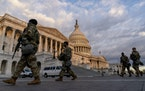ArmedNationalGuardtroops walk past the U.S. Capitol two days before the 59th Presidential Inauguration in Washington, Monday, Jan. 18, 2021.