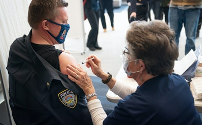 New Hope Police Chief Tim Hoyt received his COVID-19 Moderna vaccine from nurse Gloria Christensen at a vaccine clinic this month at Wayzata High Scho