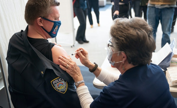 Chief Tim Hoyt of New Hope P.D. received his COVID-19 Moderna vaccine from RN Gloria Christensen at a vaccine clinic at Wayzata High School in Plymout