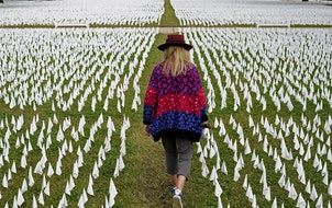FILE - In this Oct. 27, 2020, Artist Suzanne Brennan Firstenberg walks among thousands of white flags planted in remembrance of Americans who have die