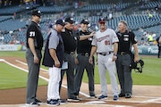 Detroit Tigers manager Ron Gardenhire, second from left, poses with his son Toby Gardenhire (81) and umpires before a game in Detroit, Sept. 17, 2018.
