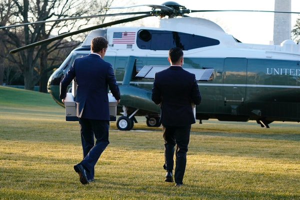 White House staff members carry boxes to Marine One before President Donald Trump leaves the White House, Wednesday, Jan. 20, 2021, in Washington. Tru