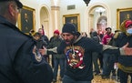 FILE - In this Jan. 6, 2021, file photo, Trump supporters gesture to U.S. Capitol Police in the hallway outside of the Senate chamber at the Capitol i