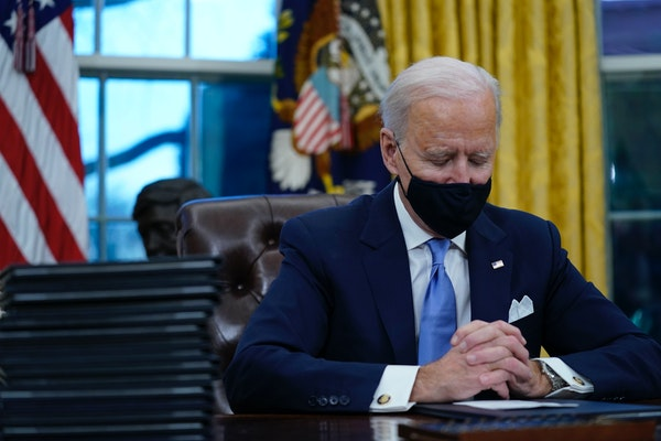 President Joe Biden pauses as he signs his first executive orders in the Oval Office of the White House on Wednesday, Jan. 20, 2021, in Washington. (