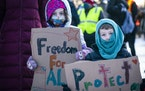Finnea Vanderford, left, 6, of Minneapolis and her brother Connor, 4, held signs during a rally and protest march on Inauguration Day.