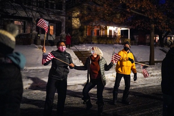Deb Pleasants, Linda Ehlers and Carl Michaud waved their flags and danced at an inaugural  celebration street party Wednesday in St. Paul.