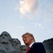 FILE — President Donald Trump watches a military plane flyover at Mount Rushmore in Keystone, S.D., July 3, 2020. The White House released the repor