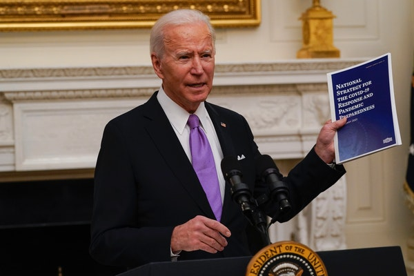 President Joe Biden held a booklet outlining his national virus strategy as he spoke today in the State Dining Room of the White House.