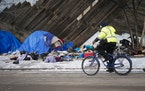 Crews cleaned up a homeless encampment on Shepherd Road in St. Paul, Minn. where fire left one person dead and one person injured. ]  Shari L. Gross �