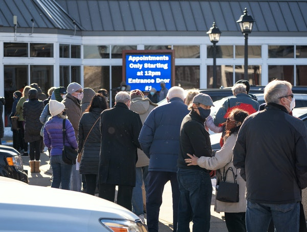 People stood in line until their appointment time and were allowed in five at a time for screening before receiving the vaccine.  Minnesota state offi