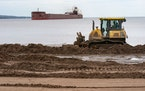 A bulldozer pushed dirt along Park Point beach while the Mesabi Miner pulled into Duluth Harbor on Tuesday afternoon. The bulldozing is part of an eff