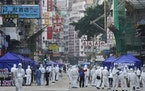 Government investigators wearing protective suits, gather in the Yau Ma Tei area, in Hong Kong, Saturday, Jan. 23, 2021. Thousands of Hong Kong reside