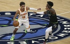 Atlanta's Trae Young handles the ball as the Timberwolves' Jaylen Nowell defends during the first half