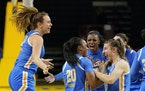 UCLA's Emily Bessoir, left, Charisma Osborne (20), Michaela Onyenwere and Chantel Horvat, right, celebrate the team's 70-66 victory over Stanford