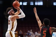 Minnesota guard Gabe Kalscheur (22) took an outside shot as Maryland guard Eric Ayala (5) reached to block in the first half.