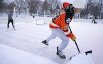 Mason Dunlap wore a Philadelphia Fliers jersey as he shoveled snow from the ice rink so he and friends could play pickup hockey Saturday at Windom Par
