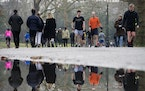 People walk through Battersea Park, in London, during England's third national lockdown to curb the spread of coronavirus, Saturday, Jan. 23, 2021.