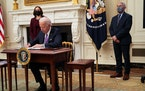 President Joe Biden signs executive orders regarding his administration's response to the COVID-19 pandemic, at the White House in Washington, Th