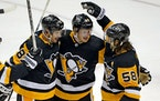 The Penguins' Jake Guentzel (59) celebrated after scoring his 100th career NHL goal with Sidney Crosby (87) and Kris Letang during the third period