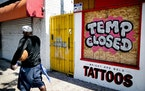 A tattoo parlor on El Cajon Boulevard has its windows boarded up on May 28, 2020, in San Diego, Calif. Sophisticated hackers, identity thieves and ov
