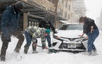 Good Samaritans stop to help dig out a stuck car along 13th Street during a winter storm in downtown Lincoln, Neb. on Monday, Jan. 25, 2021.