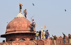 Sikhs hoist a Nishan Sahib, a Sikh religious flag, on a minaret of the historic Red Fort monument in New Delhi, India, Tuesday, Jan. 26, 2021. Tens of
