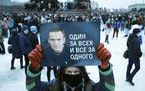 "A man holds a poster with a portrait of Russian opposition leader Alexei Navalny and the message ""One for all and all for one"" during a protest Sa"