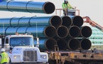 FILE - In this May 9, 2015, file photo, workers unload pipes in Worthing, S.D., for the Dakota Access oil pipeline that stretches from the Bakken oil