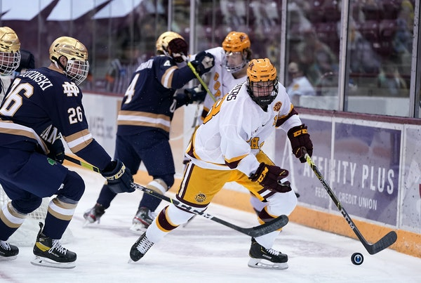 Gophers forward Mason Nevers controlled the puck against Notre Dame defenseman Zach Plucinski during a game at Mariucci Arena on Jan. 15.