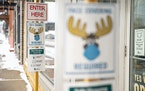 Moose-themed signs are plastered on store fronts around Grand Marais, Minn. encouraging people to wear masks and practice social distancing.