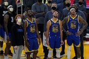 Andrew Wiggins (22), Stephen Curry (30) and Kelly Oubre Jr. (12) watch a replay on the scoreboard with head coach Steve Kerr, middle top, against the