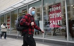 A passer-by walks past a store closing sign, right, in the window of a department store, Tuesday, Oct. 27, 2020, in Boston. The U.S. economy grew at a