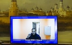 Russian opposition leader Alexei Navalny appears on a TV screen during a live session with the court during a hearing of his appeal in a court in Mosc
