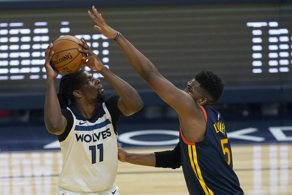 Wolves center Naz Reid shoots on Golden State's Kevon Looney on Wednesday night.