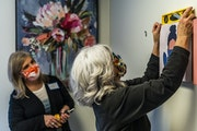 Designer Lisa Ball put up a new painting in a former office space, assisted by Bridget Zak. The volunteers turned institutional decor into colorful an
