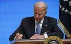President Joe Biden signs an executive order in Washington on Jan. 25.